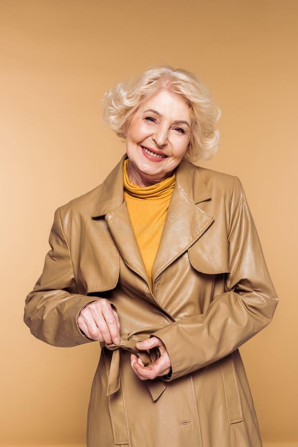 het glimlachen van modieuze hogere vrouwen bindende riem van leertrenchcoat stock afbeeldingen