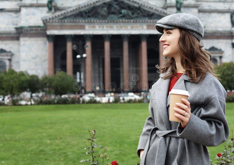Het glimlachen van modieuze jonge vrouw het drinken koffie terwijl het lopen op een stadsstraat stock fotografie