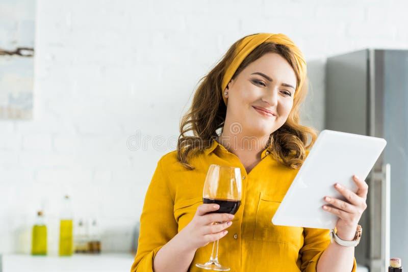 het glimlachen van het mooie glas van de vrouwenholding rode wijn en het gebruiken van tablet stock fotografie