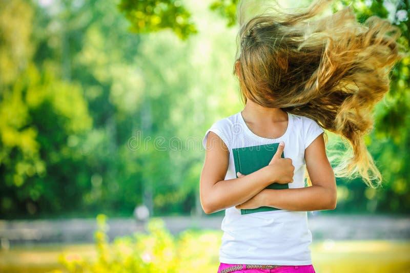 Het glimlachen van mooie tienerwind met vliegend haar stock afbeelding