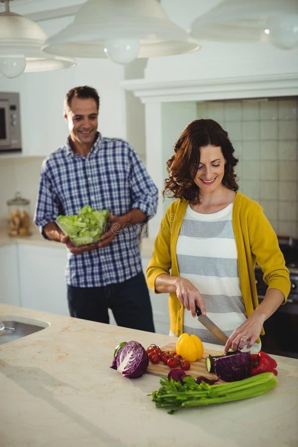 Het glimlachen van paar hakkende groenten in de keuken royalty-vrije stock foto's