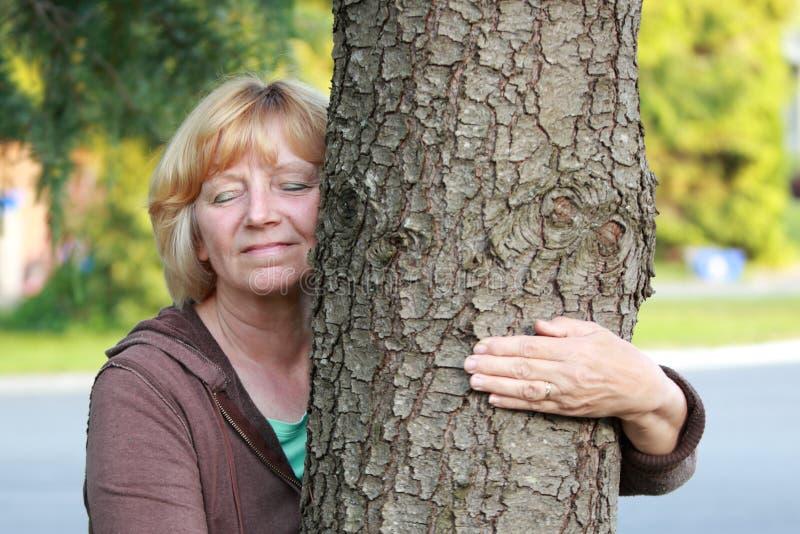 Het glimlachen van rijp vrouwenwapen rond boom royalty-vrije stock afbeeldingen
