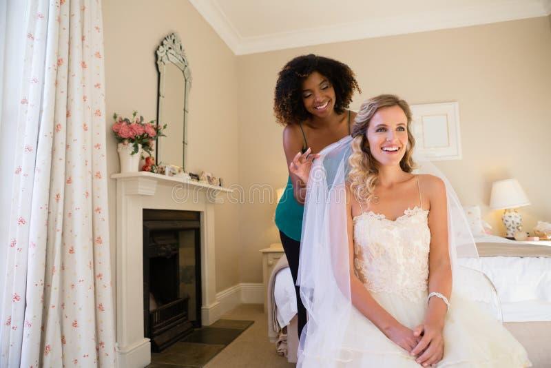 Het glimlachen van schoonheidsspecialist het aanpassen sluier van bruidzitting op bed royalty-vrije stock afbeeldingen