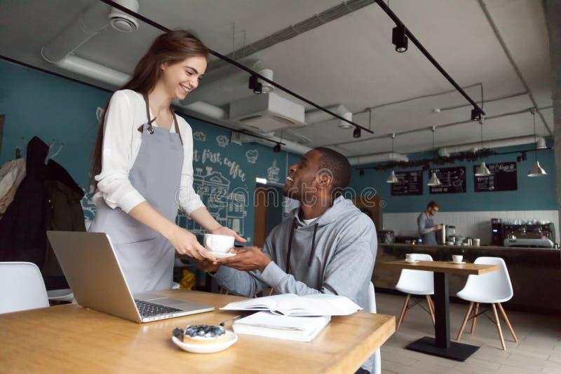 Het glimlachen van serveerster dienende koffie aan zwarte millennial koffievisito royalty-vrije stock fotografie