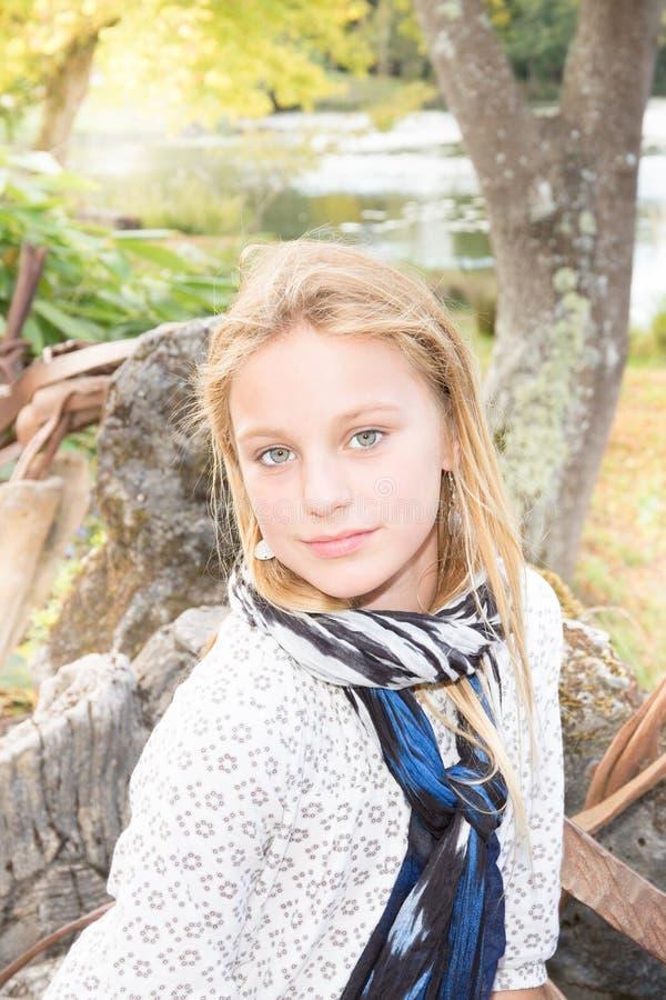 Het glimlachen van tiener blonde dragende modieuze kleren in park het bekijken camera stock foto's