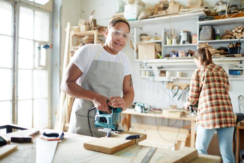 Het glimlachen van timmermans scherpe plank met elektrische zaag stock afbeeldingen