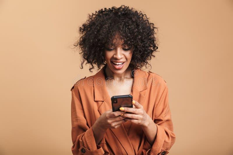 Het glimlachen van vrij Afrikaans vrouw het schrijven bericht op smartphone royalty-vrije stock fotografie
