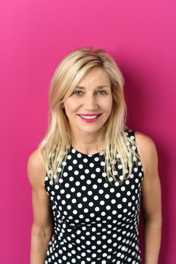 Het glimlachen van vrij Blonde Volwassen Dame Against Pink stock fotografie