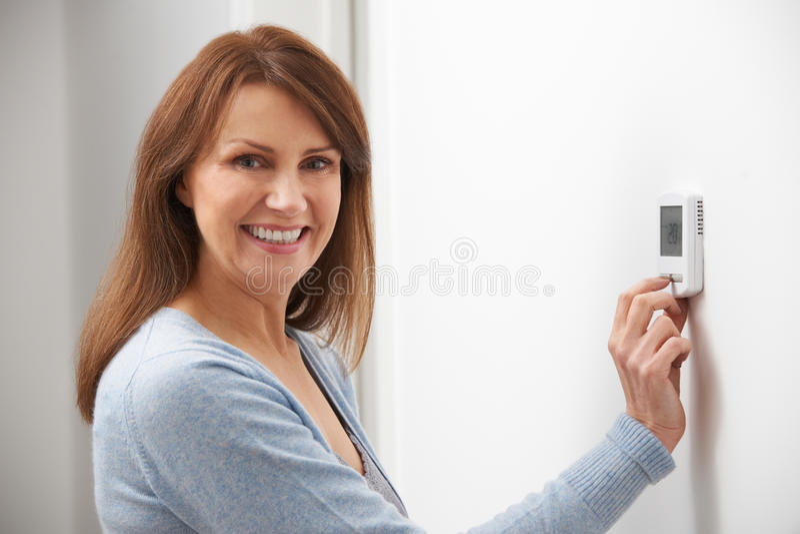 Het glimlachen van Vrouw het Aanpassen Thermostaat op Huis Verwarmingssysteem stock foto's