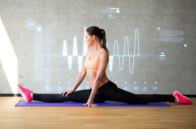 Het glimlachen van vrouw het uitrekken zich been op mat in gymnastiek stock fotografie