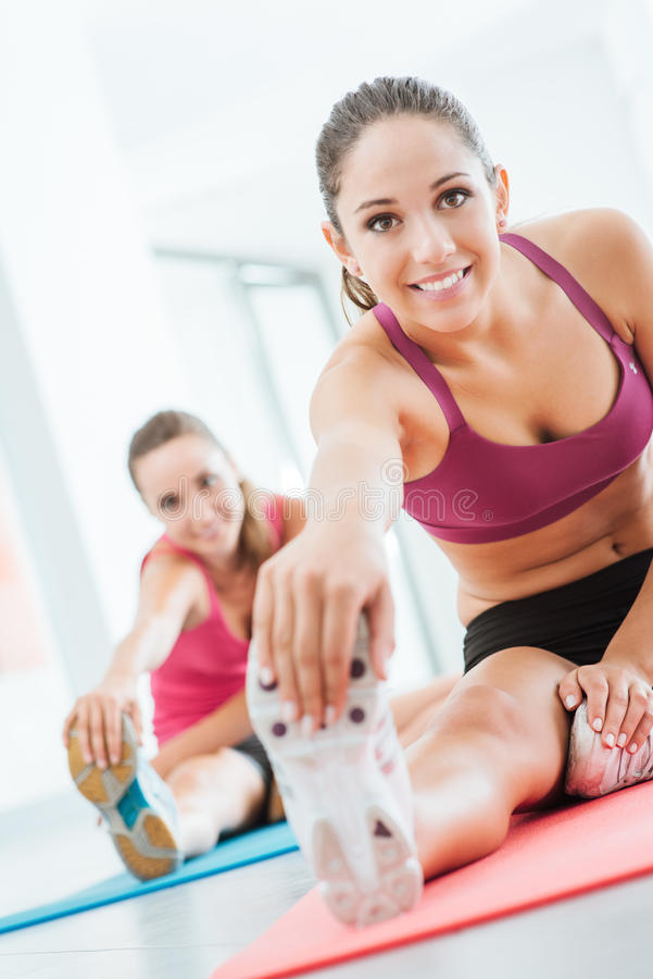 Het glimlachen van vrouw het uitrekken zich benen bij de gymnastiek royalty-vrije stock fotografie