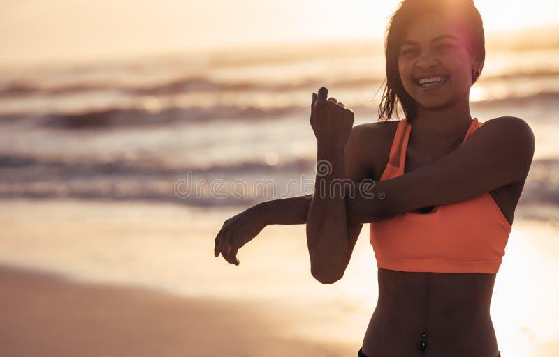 Het glimlachen van vrouw het uitrekken zich wapens bij het strand royalty-vrije stock afbeeldingen
