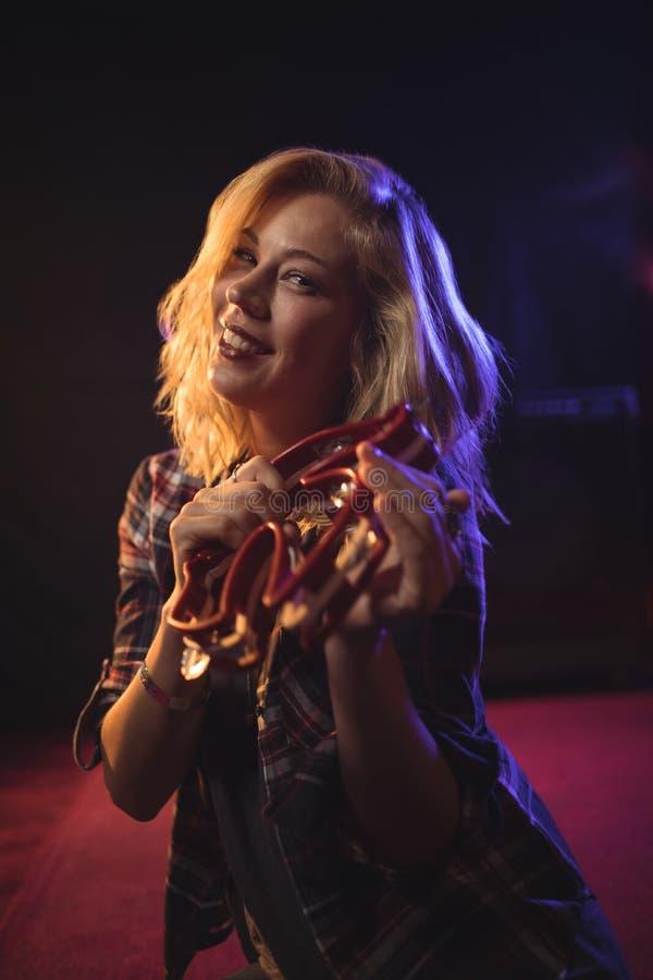 Het glimlachen van vrouwelijke musicus het spelen tamboerijn in nachtclub stock foto