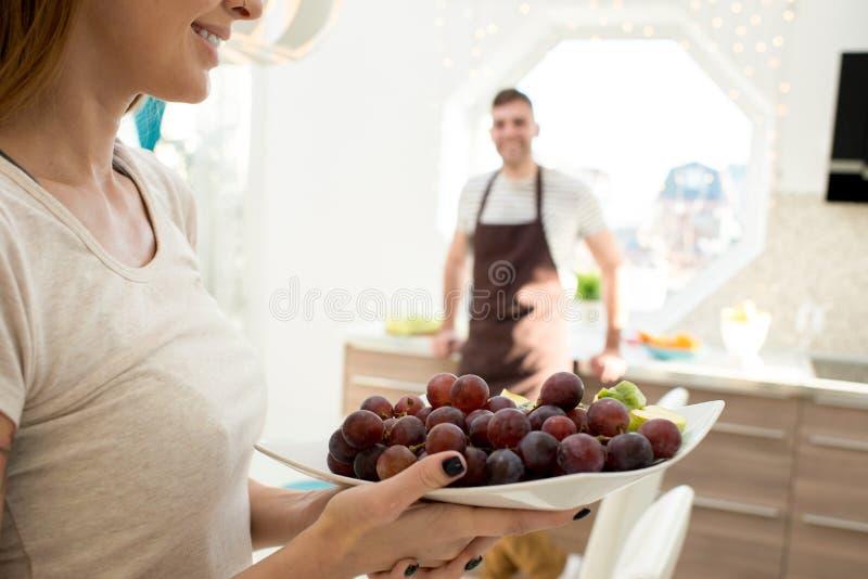 Het glimlachen van vrouwen dragende kom met druiven stock afbeelding
