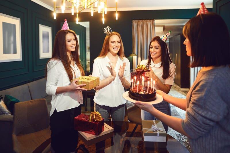 Het glimlachen van vrouwen met stelt en cake die partij hebben voor stock foto