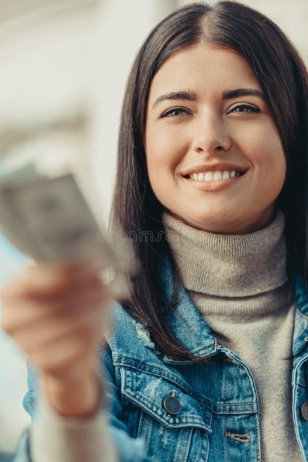 het glimlachen van vrouwen outstretching bos van dollars royalty-vrije stock foto's