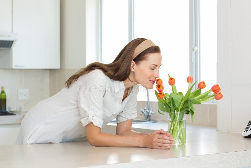 Het glimlachen van vrouwen ruikende bloemen in keuken stock afbeelding