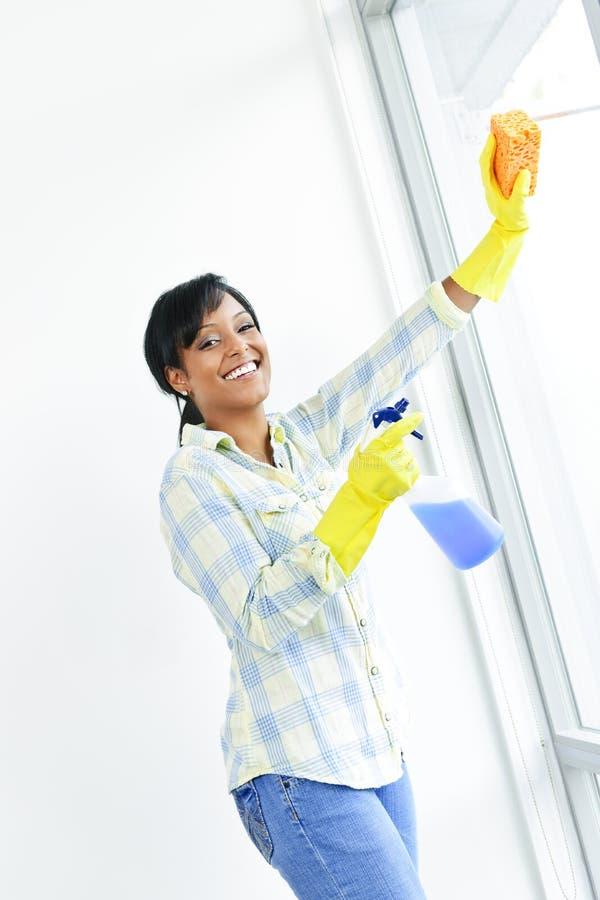 Het glimlachen van vrouwen schoonmakende vensters stock foto's