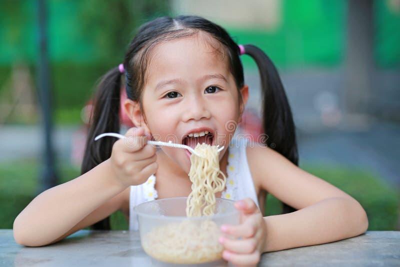 Het glimlachen van weinig Aziatisch jong geitjemeisje die Onmiddellijke noedels in de ochtend eten bij de tuin royalty-vrije stock afbeelding