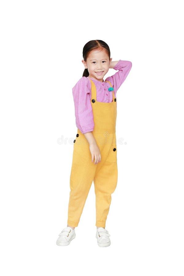 Het glimlachen van weinig Aziatisch jong geitjemeisje in roze-gele grove calico's stelt geraakt haar houdt terug op witte achterg stock foto