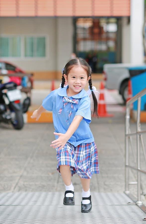 Het glimlachen van weinig Aziatisch jong geitjemeisje in school eenvormige het lanceren metaaltrede stock fotografie