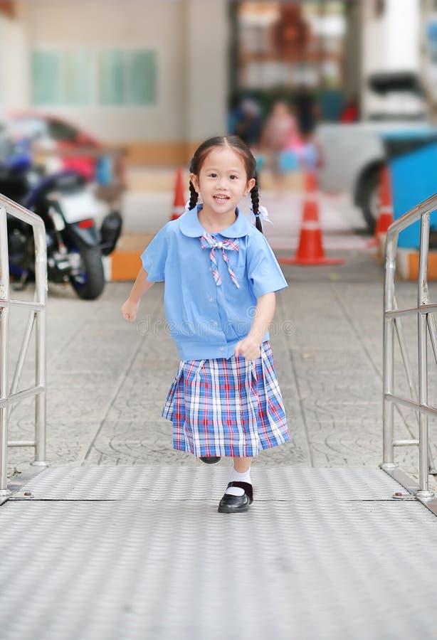 Het glimlachen van weinig Aziatisch jong geitjemeisje in school eenvormige het lanceren metaaltrede stock foto
