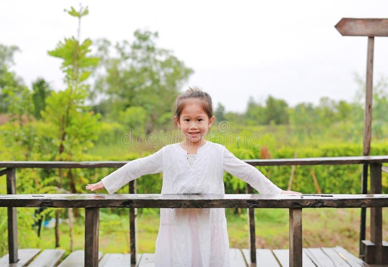 Het glimlachen van weinig Aziatisch kindmeisje die open wapens op houten brug posten bij de aard stock foto's