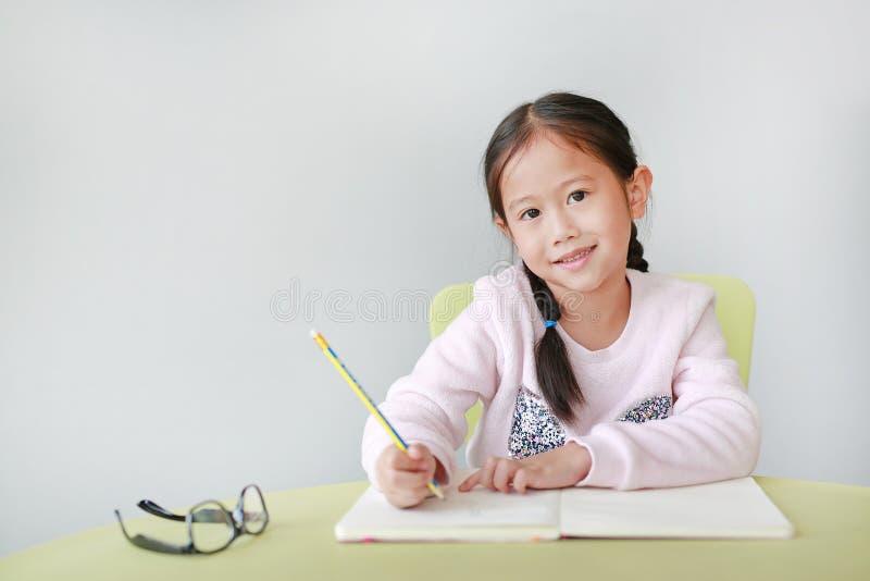 Het glimlachen van weinig Aziatisch kindmeisje schrijft in een boek of een notitieboekje met potlood op lijst in klaslokaal tegen royalty-vrije stock fotografie