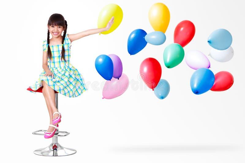 Het glimlachen van weinig Aziatische meisjeszitting stock foto