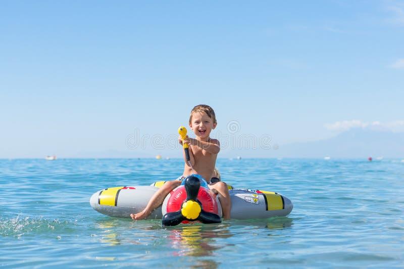Het glimlachen van weinig babyjongen die in het overzees op het luchtvliegtuig spelen Positieve menselijke emoties, gevoel, royalty-vrije stock foto's