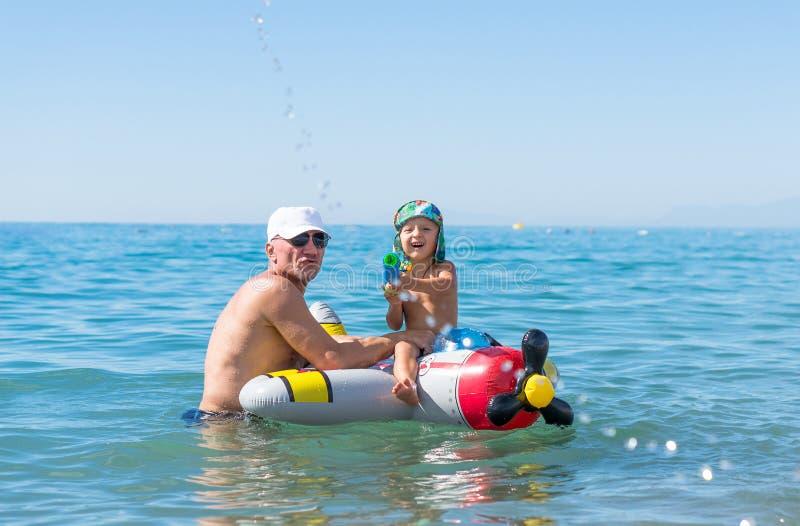Het glimlachen van weinig babyjongen die met grootmoeder en grootvader in het overzees op het luchtvliegtuig spelen Positieve men stock afbeelding
