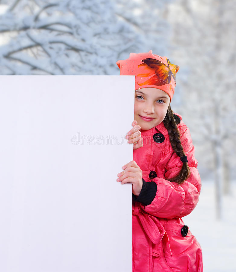 Het glimlachen van weinig jong meisjeskind in de winter kleedt jasjelaag en hoed houdend een lege witte raad van de aanplakbordba royalty-vrije stock foto