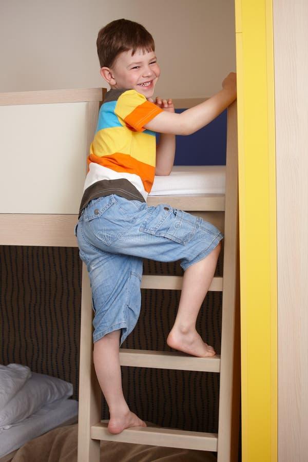 Het glimlachen van weinig jongen die de ladder van stapelbed uitgaat stock afbeelding