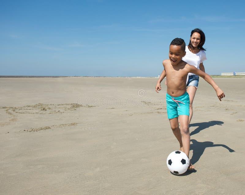 Het glimlachen van weinig jongen die met bal op strand spelen royalty-vrije stock afbeelding