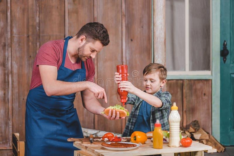 Het glimlachen van weinig jongen met vader kokende hotdog bij binnenplaats stock fotografie