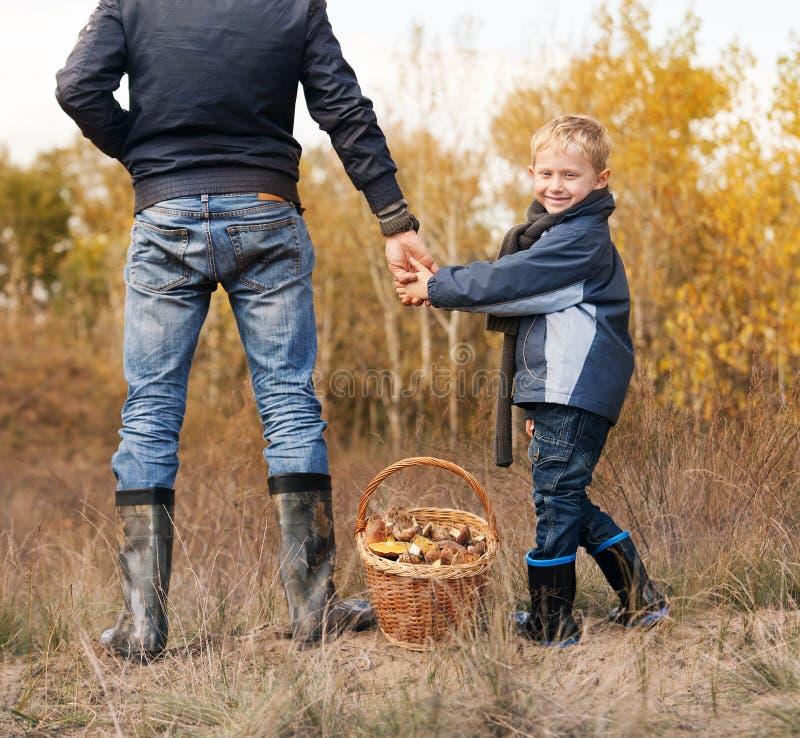 Het glimlachen van weinig jongen met zijn vader op paddestoelen het plukken royalty-vrije stock foto's