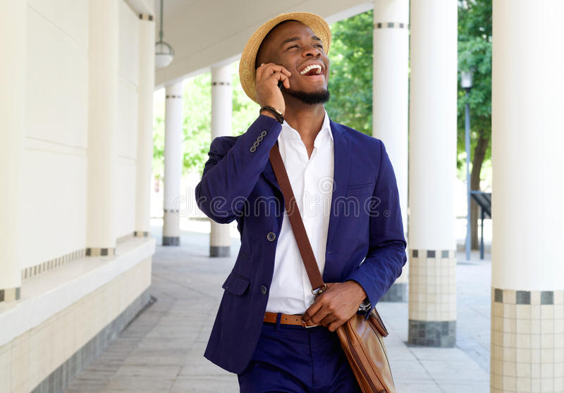 Het glimlachen van zwarte kerel die en op mobiele telefoon lopen spreken stock afbeeldingen