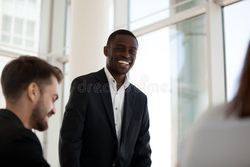 Het glimlachen van zwarte mentortribune die met werknemers tijdens vergadering spreken royalty-vrije stock fotografie
