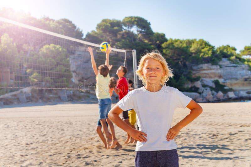Het glimlachen volleyball van het jongens het speelstrand met vrienden stock foto's