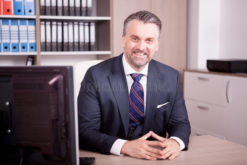 Het glimlachen volwassen CEO bij zijn bureau in bureau stock foto's
