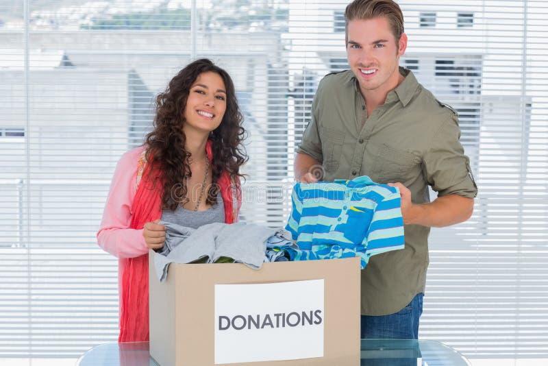 Het glimlachen vrijwilligers het nemen kleedt zich van schenkingendoos stock foto