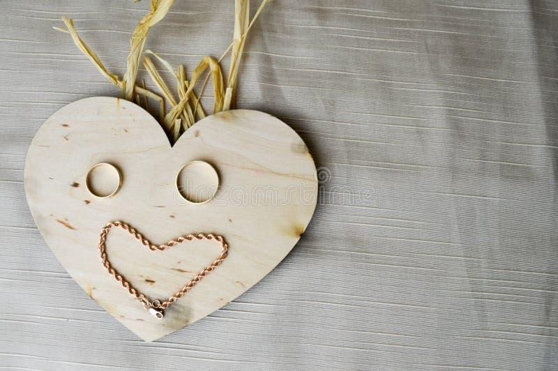 Het glimlachen, vrolijk, vriendelijk gezicht met strohaar maakte van een houten hart aan de Dag van Valentine ` s, huwelijks goud stock fotografie