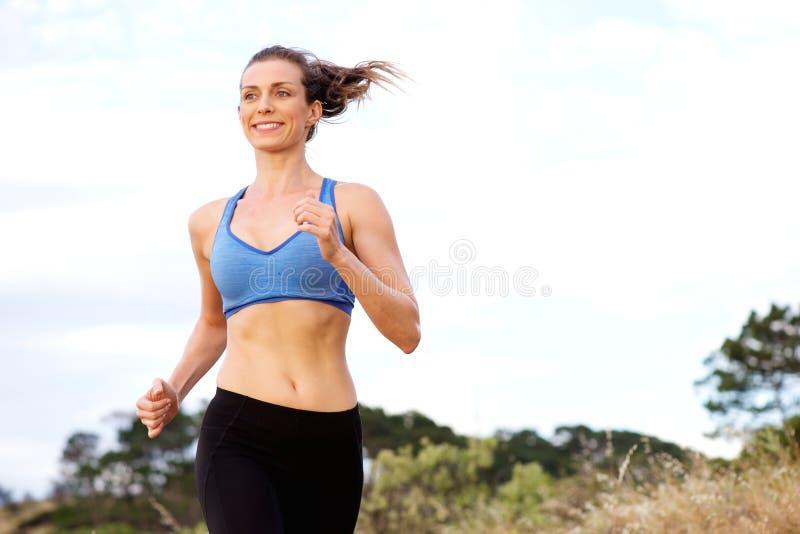 Het glimlachen vrouw buiten in werking gesteld genieten van stock foto