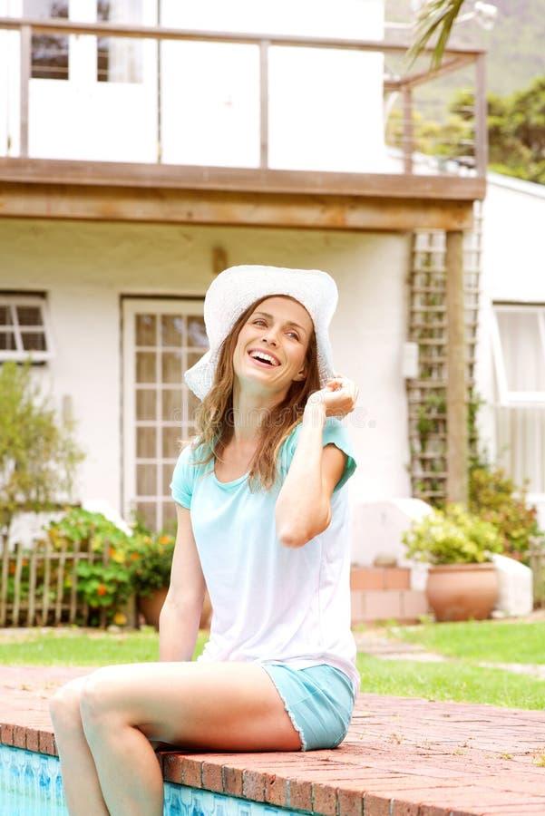 Het glimlachen vrouw het ontspannen door pool royalty-vrije stock foto's
