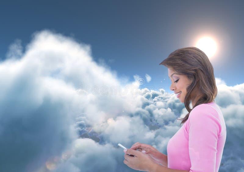 Het glimlachen vrouw het texting met wolken en zon op achtergrond royalty-vrije stock foto's