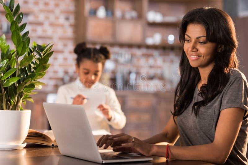Het glimlachen vrouw het typen op laptop met dochter die thuiswerk dichtbij langs doen royalty-vrije stock afbeelding