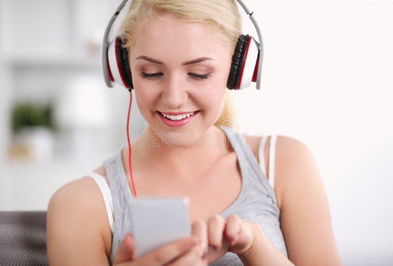 Het glimlachen vrouw het luisteren muziek in hoofdtelefoons en het gebruiken van smartphone stock fotografie