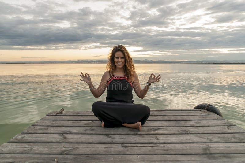 Het glimlachen vrouw het praktizeren meditatie in de positie van de lotusbloemyoga inzake een houten pier stock afbeeldingen