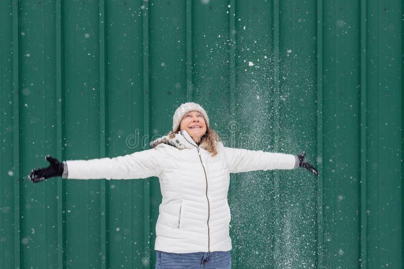 Het glimlachen vrouw het spelen in verse sneeuw buiten royalty-vrije stock afbeeldingen