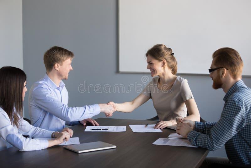 Het glimlachen vrouwelijk en mannelijk partnershandenschudden tevreden met inh. royalty-vrije stock foto's